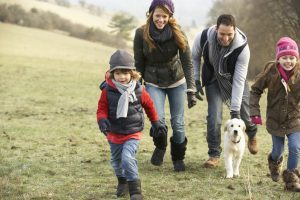 Family and dog having fun in the country in winter